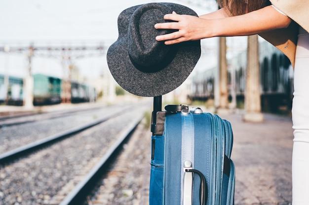 Vrouw die haar hoed op haar koffer op het treinstation plaatst. Premium Foto