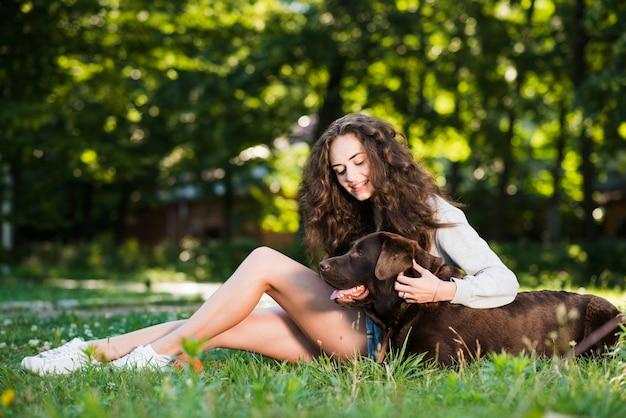 Vrouw die haar hondzitting op gras in park tikt Gratis Foto