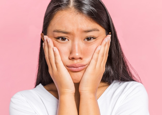 Vrouw die haar hoofd in palmen houdt en camera bekijkt Gratis Foto