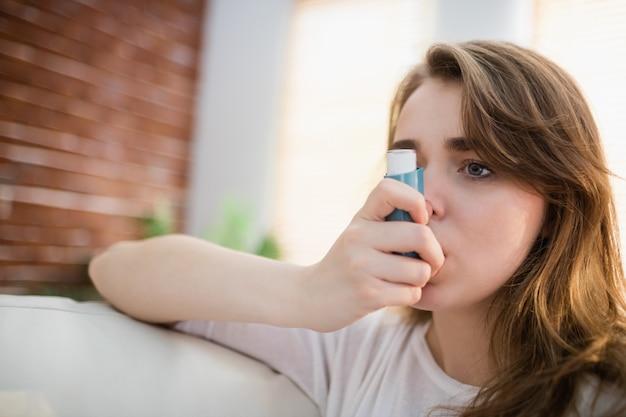 Vrouw die haar inhaleertoestel op laag in de woonkamer met behulp van Premium Foto
