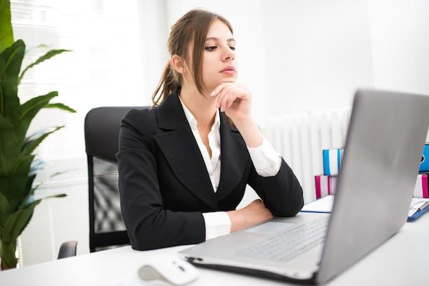Vrouw die haar laptop met behulp van op het werk Premium Foto