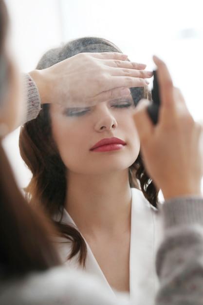 Vrouw die haar make-up laten doen door een visagist Gratis Foto