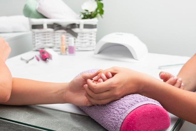 Vrouw die haar manicure heeft die bij de salon met exemplaarruimte wordt gedaan Gratis Foto