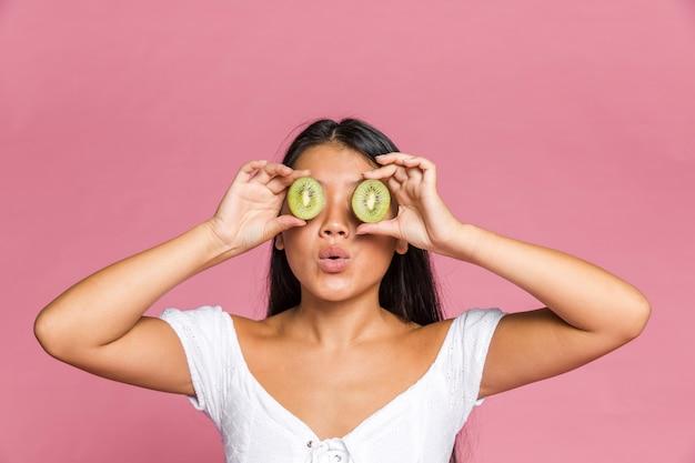 Vrouw die haar ogen behandelt met kiwi op roze oppervlakte Gratis Foto