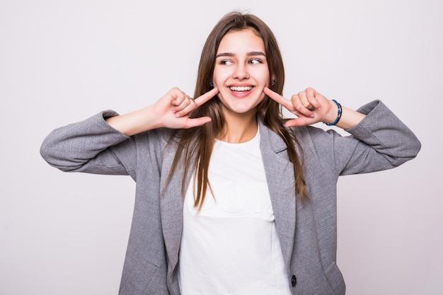 Vrouw die haar perfecte rechte witte tanden op witte achtergrond toont Gratis Foto