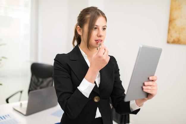 Vrouw die haar tablet gebruiken als spiegel om op wat lippenstift in het bureau te zetten Premium Foto