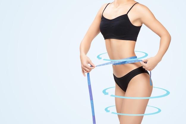 Vrouw die haar taille meet door blauwe maatregelenband Premium Foto