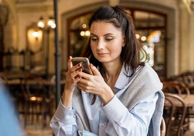 Vrouw die haar telefoon controleert in het restaurant Gratis Foto
