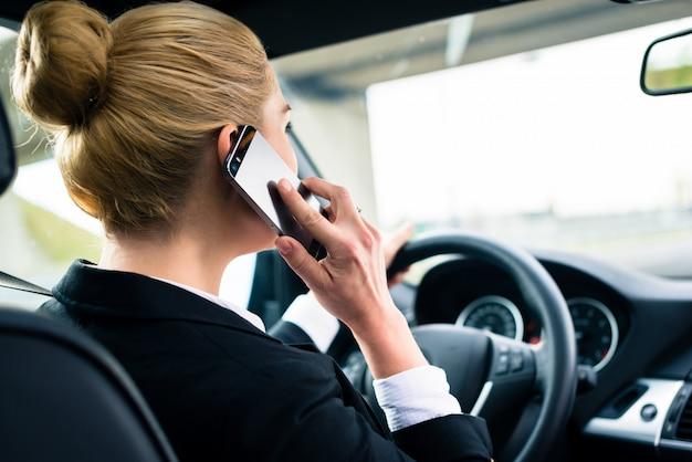Vrouw die haar telefoon met behulp van terwijl het drijven van de auto Premium Foto