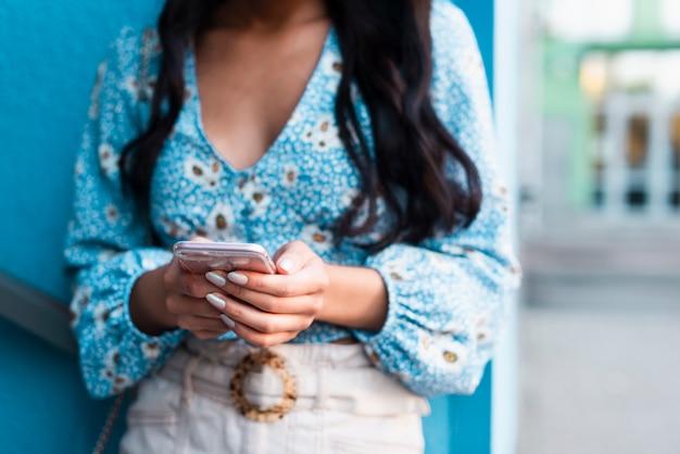 Vrouw die haar telefoon met blauwe achtergrond met behulp van Gratis Foto