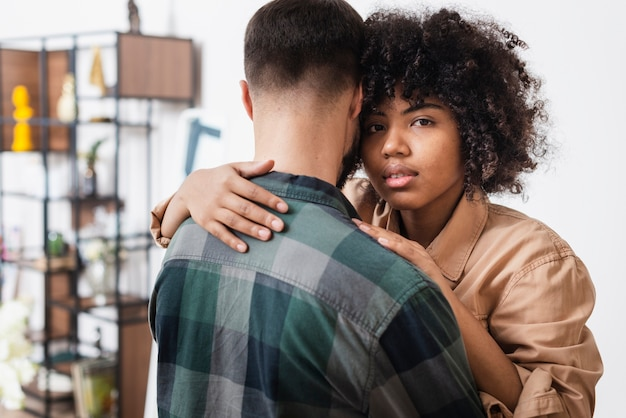 Vrouw die haar vriend omhelst en fotograaf bekijkt Gratis Foto