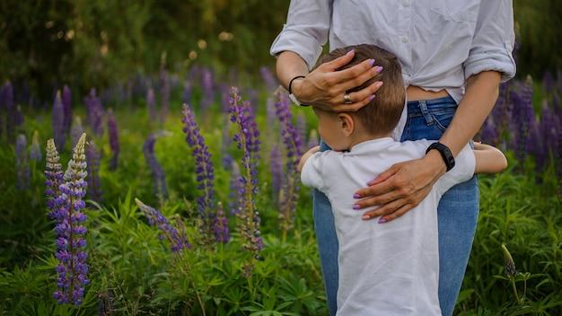 Vrouw die haar zoon koestert die zich op het purpere bloemengebied bevindt Premium Foto