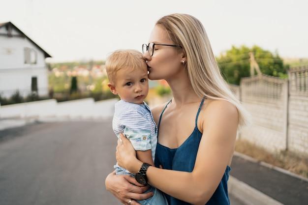 Vrouw die haar zoon vervoert en op zijn voorhoofd kust. Gratis Foto