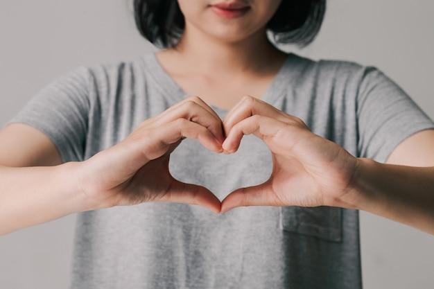 Vrouw die handen in hartvorm, donatie, gelukkige liefdadigheidsvrijwilliger, wereldhartdagconcept maakt Premium Foto