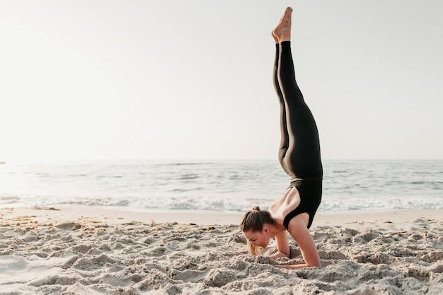 Vrouw die handstand in zand doet dichtbij oceaan het praktizeren yogaasana Premium Foto