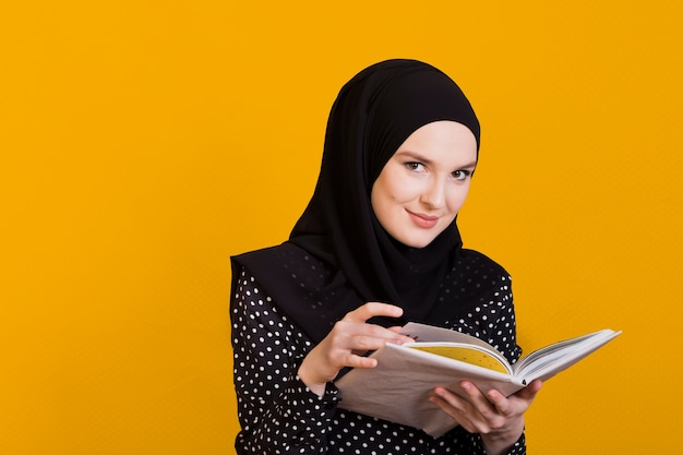 Vrouw die het boek van de cameraholding in hand oppervlak bekijkt Gratis Foto