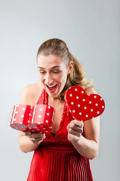 Vrouw die het geschenk opent en is blij Premium Foto