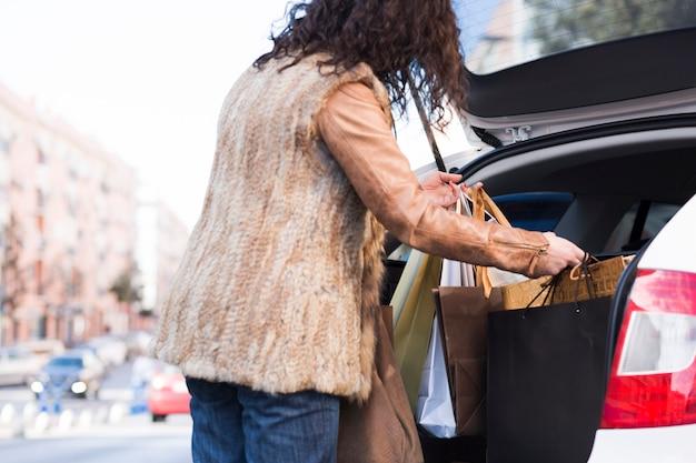 Vrouw die het winkelen zakken in auto zet Gratis Foto