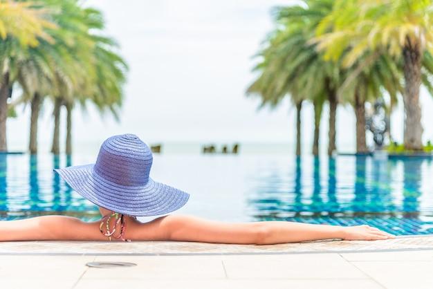 Vrouw die hoed in de toevlucht van het hotelpool draagt Gratis Foto
