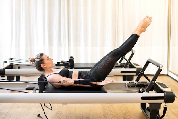 Vrouw die honderd pilates oefening op hervormerbed doet Premium Foto