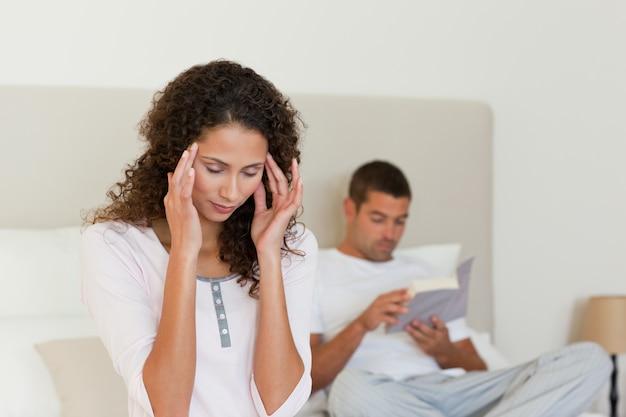 Vrouw die hoofdpijn heeft terwijl haar echtgenoot leest Premium Foto