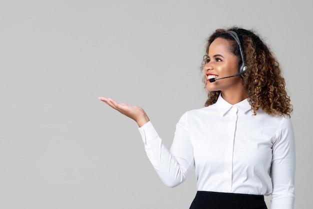 Vrouw die hoofdtelefoons draagt als call centrepersoneel met open hand Premium Foto