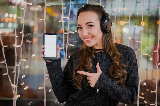 Vrouw die hoofdtelefoons draagt die telefoon tonen dichtbij kerstmislichten Gratis Foto