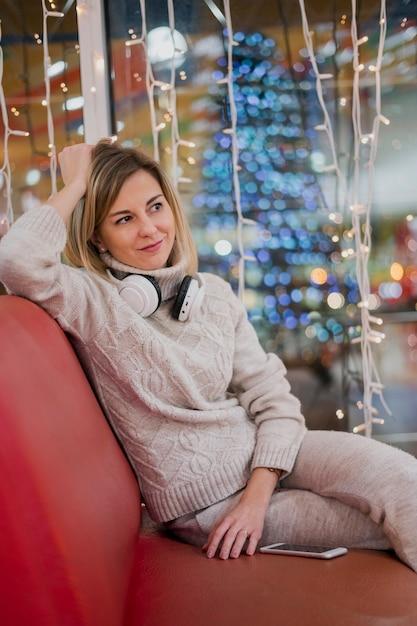 Vrouw die hoofdtelefoons rond de hals draagt en op laag dichtbij kerstmislichten zit Gratis Foto
