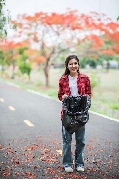 Vrouw die huisvuil in een zwarte zak verzamelt. Gratis Foto