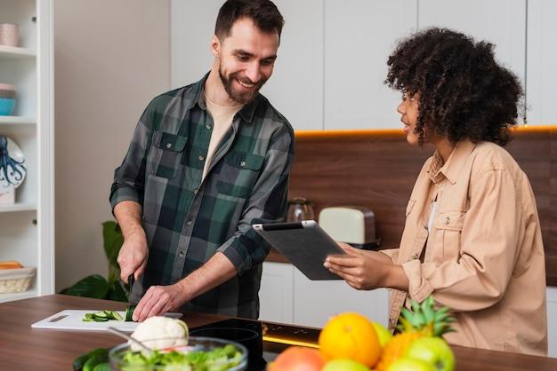 Vrouw die iets op tablet tonen aan man het koken Gratis Foto