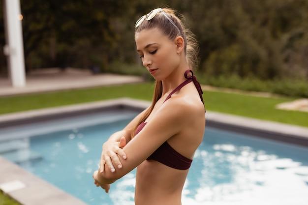 Vrouw die in bikini zonneschermlotion op haar lichaam toepast dichtbij poolside Gratis Foto