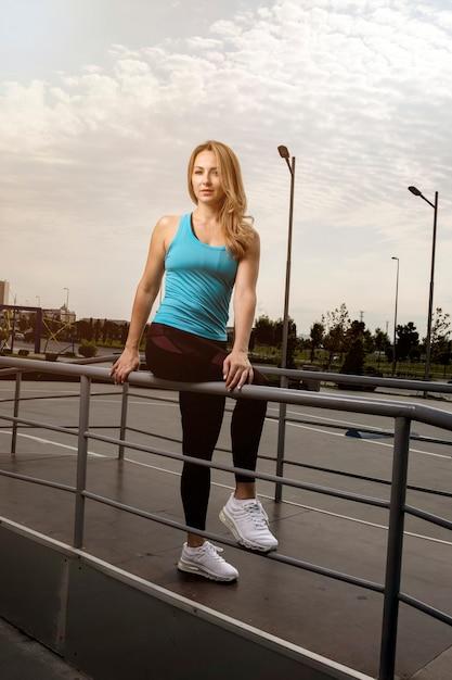 Vrouw die in blauwe en zwarte fitnessuitrustingen vandaar op metaal zit. Gratis Foto