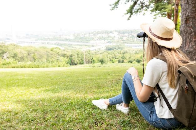 Vrouw die in bos door verrekijkers kijkt Gratis Foto