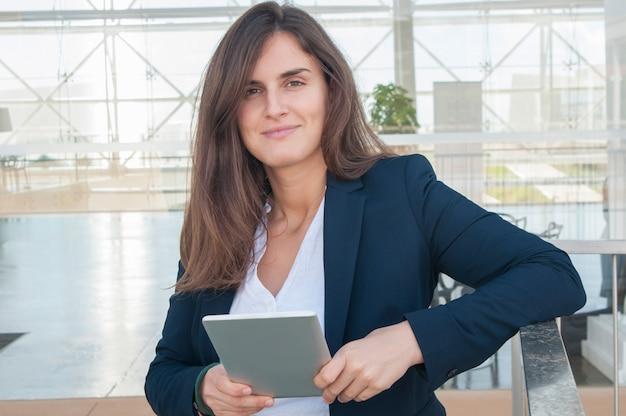 Vrouw die in bureau camera bekijkt, die tablet in handen houdt Gratis Foto