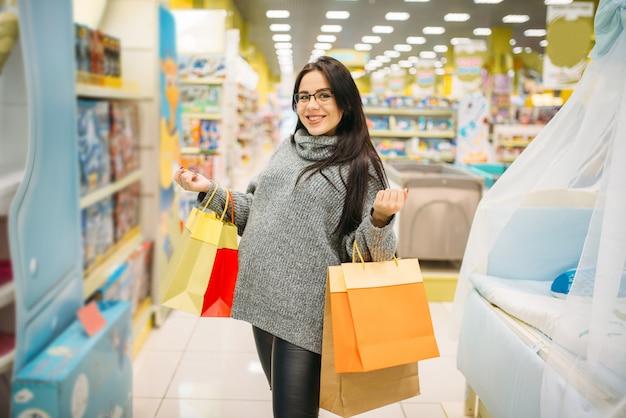 Vrouw die in de opslag voor zwangere vrouwen winkelt. toekomstige moeder in winkel met goederen voor nieuwe brandwonden Premium Foto