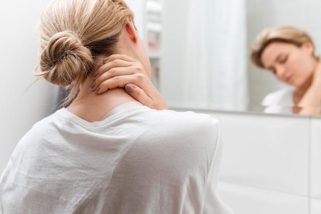 Vrouw die in de spiegel kijkt die halspijn heeft Gratis Foto