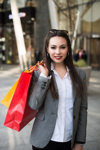 Vrouw die in een stadsstraat loopt met het winkelen zakken Premium Foto