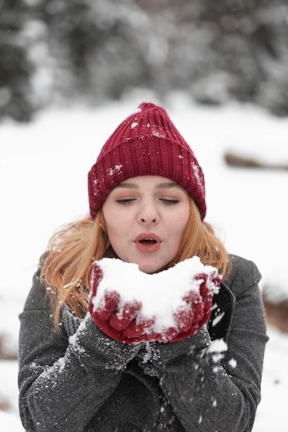 Vrouw die in een stapel van sneeuw blaast Gratis Foto