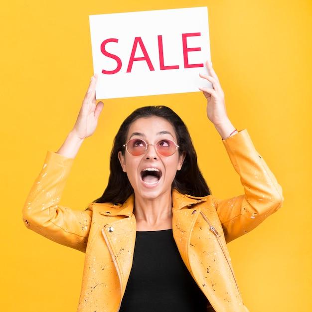 Vrouw die in geel jasje een middelgroot schot van de verkoopbanner houdt Gratis Foto