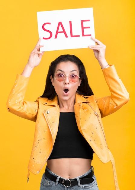 Vrouw die in geel jasje een verkoopbanner houdt Gratis Foto