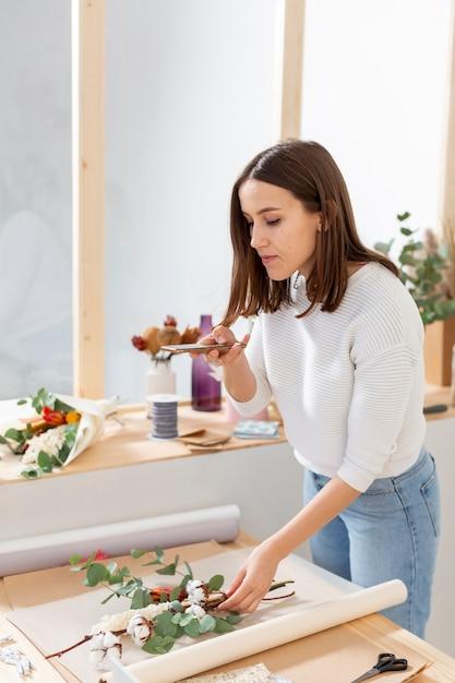 Vrouw die in haar bloemenwinkel een boeket maakt Gratis Foto