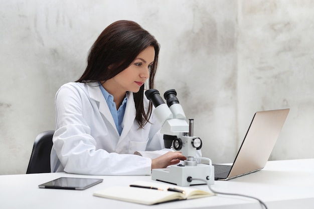 Vrouw die in het laboratorium met een microscoop werkt Gratis Foto
