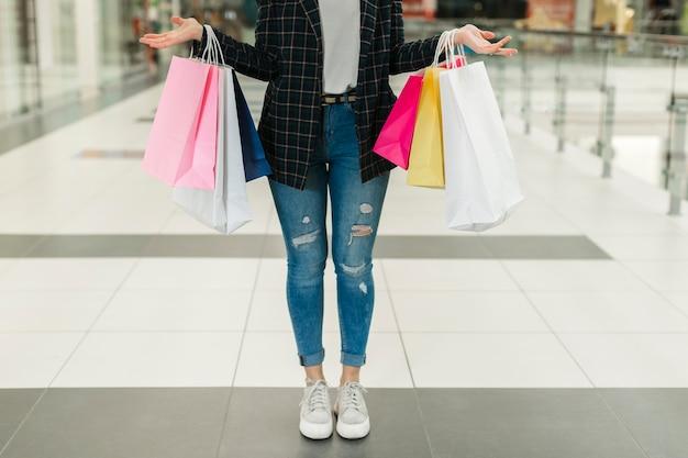 Vrouw die in jeans het winkelen zakken houdt Gratis Foto