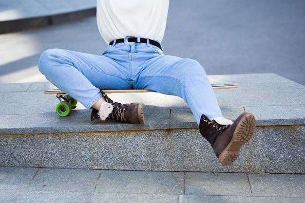 Vrouw die in jeans op longboard zit Gratis Foto