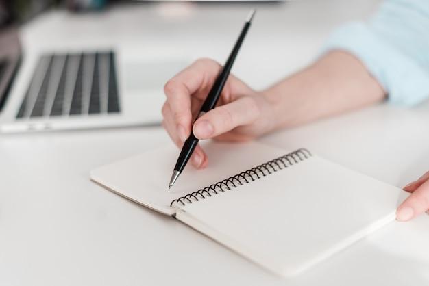 Vrouw die in notitieboekje schrijft Premium Foto