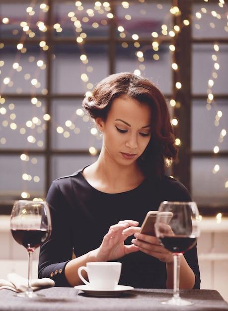Vrouw die in restaurant een wijnglas houdt Gratis Foto