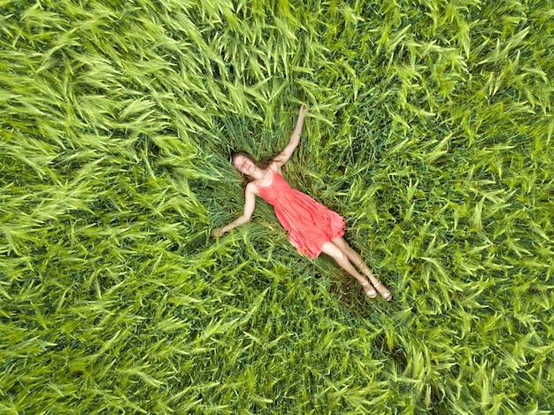 Vrouw die in rode kleding op groen tarwegebied legt Premium Foto