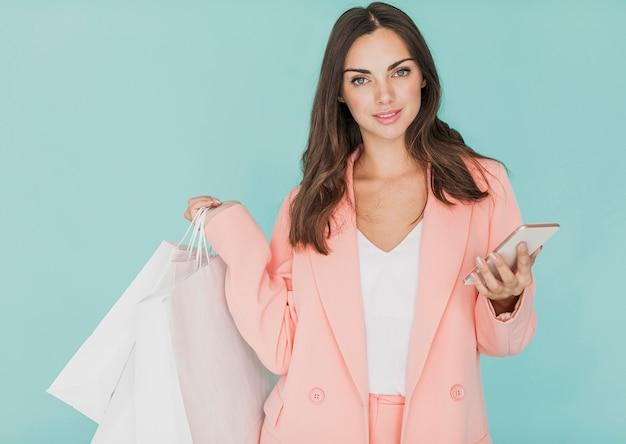 Vrouw die in roze jasje aan de camera kijkt Gratis Foto