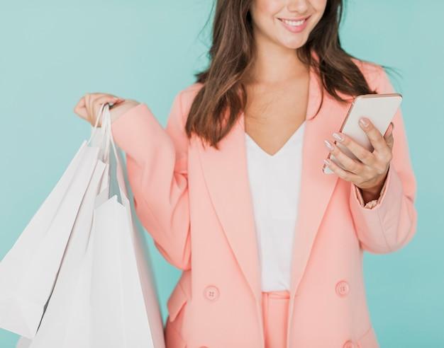 Vrouw die in roze jasje bij smartphone glimlacht Gratis Foto