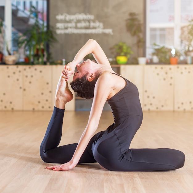 Vrouw die in studio uitwerkt die uitrekkende oefeningszitting doet in houding van de yoga de éénbenige koning pigeon Premium Foto